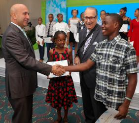 File photo shows R. Danny Williams (2nd right), chairman, Sagicor Foundation and Sagicor Group CEO Christopher Zacca (left) greet recipients of the Sagicor Foundation scholarship.