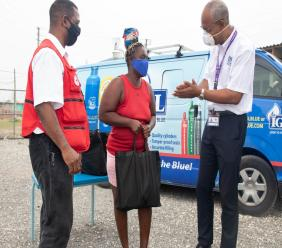 Peter Graham (right), Managing Director of IGL, shares words of encouragement with Kimesha Thorpe of Callaloo Mews after presenting her with a package of groceries courtesy of the Ignite IGL Foundation. Looking on is Michael Gordon, Chairman of the Emergency Services Council, Jamaica Red Cross.