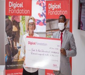 Sur la photo, l'un des finalistes, reçevant son chèque de 250 mille gourdes. Photo : Fondation Digicel.