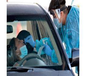 In this June 27, 2020, photo, people are tested in their in vehicles in Phoenix's western neighborhood of Maryvale in Phoenix for free COVID-19 tests organized by Equality Health Foundation, which focuses on care in underserved communities. Arizona's Republican governor shut down bars, movie theaters, gyms and water parks Monday, June 29. (AP Photo/Matt York)
