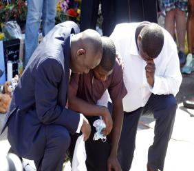Quincy Mason, center, the son of George Floyd, and family attorney Ben Crump, left, kneel, Wednesday, June 3, 2020 as they visited the site of a memorial in Minneapolis where Floyd was arrested on May 25 and died while in police custody.(AP Photo/Jim Mone)