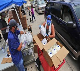 Wearing masks amid concerns of the spread of COVID-19, volunteers Karen Cooperstein, right, and Edwin Chinchilla, left, prepare food for the pubic during a drive through food pantry distribution by Catholic Charities in Dallas, Thursday, July 2, 2020. (AP Photo/LM Otero)