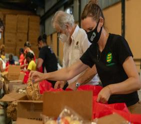 Seprod Foundation and Musson Foundation Chair Melanie Subratie (foreground) and CB Facey Foundation Chairman and Chairman and CEO of PanJam Investment Limited Stephen Facey assist the Jamaica Red Cross to prepare 2,939 packages at the Private Sector Organisation of Jamaica (PSOJ) COVID-19 Relief Warehouse in Three Miles on Wednesday July 1, 2020.