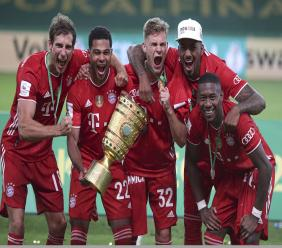 Bayern Munich players celebrate with the trophy after winning the German football cup (DFB Pokal) final match Bayer Leverkusen in Berlin, Germany, Saturday, July 4, 2020. (AP Photo/Michael Sohn).