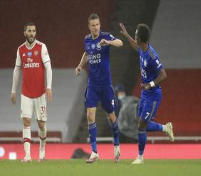 Leicester's Jamie Vardy, centre, is congratulated by teammate Demarai Gray after scoring a late goal during the English Premier League football match against Arsenal at the Emirates Stadium in London, England, Tuesday, July 7, 2020. (AP Photo/Adam Davy,Pool).