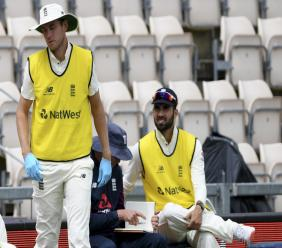 England's Stuart Broad, left, wears a disposable pair of gloves as a precaution against the coronavirus during the third day of the first cricket Test match against the West Indies, at the Ageas Bowl in Southampton, England, Friday, July 10, 2020. (Mike Hewitt/Pool via AP).