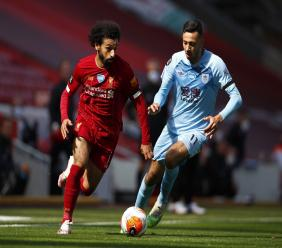Liverpool's Mohamed Salah, left, takes the ball past Burnley's Dwight McNeil during their English Premier League football match at Anfield, Liverpool, England, Saturday, July 11, 2020. (Clive Brunskill/ Pool via AP).
