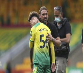 Norwich City's head coach Daniel Farke comforts Josh Martin at the end of the English Premier League football match against West Ham at the Carrow Road stadium in Norwich, England, Saturday, July 11, 2020. (Alex Pantling/Pool via AP).