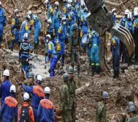 Rescuers search for missing persons at the site of a landslide in Tsunagi town, Kumamoto prefecture, southern Japan Monday, July 6, 2020. Rescue operations continued and rain threatened wider areas of the main island of Kyushu. (Takuto Kaneko/Kyodo News via AP)