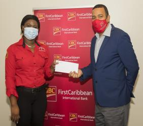 Nigel Holness (right), Managing Director of CIBC FirstCaribbean International Bank, presents the bank's cheque to Mickel Jackson, Grants Manager of the Jamaica AIDS Support for Life. The bank's donation will help fund care packages for persons living with HIV/AIDS and the purchase of Personal Protective Equipment (PPE) for employees of three facilities run by JAS across Jamaica.