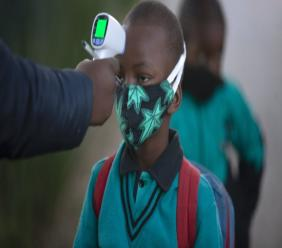 A pupil's temperature is checked on returning to school in Johannesburg, Tuesday July 7, 2020, as more learners were permitted to return to class. Schools were shut down in March prior to a total country lockdown in a bid to prevent the spread of coronavirus and are now slowly being re-opened. (AP Photo/Denis Farrell)