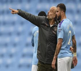 Manchester City's head coach Pep Guardiola, left, talks with Kyle Walker during the English Premier League football match against Newcastle at the Ethiad Stadium in Manchester, England, Wednesday, July 8, 2020. (Oli Scarff/Pool via AP)