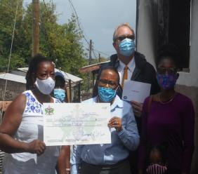 Orricia Denbow-Bullen (right) presenting cheque to Lucella Joseph