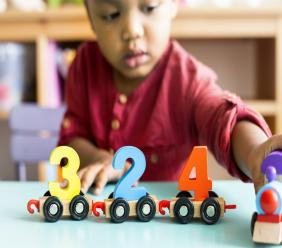 Little boy playing mathematics wooden toy at day care. (Photo: iStock)