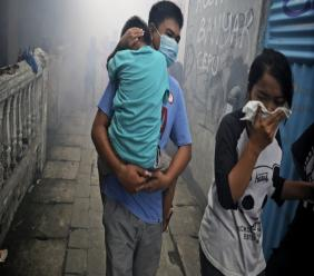 People move away as health workers fumigate a slum to prevent an outbreak of dengue fever in Jakarta, Indonesia, on Monday, March 23, 2020.  (AP Photo/Dita Alangkara)