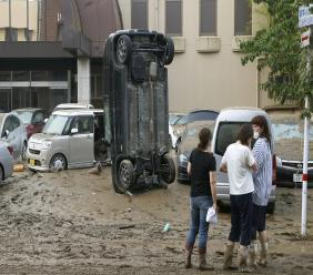 A car stands vertically on a muddy road after being washed away by flood, in Hitoyoshi, Kumamoto prefecture, southwestern Japan, Sunday, July 5, 2020. Heavy rain in the Kumamoto region triggered flooding and mudslides Saturday and left dozens still being stranded at their homes and other facilities. (Kyodo News via AP)