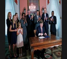 Mississippi Republican Gov. Tate Reeves signs the bill retiring the last state flag in the United States with the Confederate battle emblem, at the Governor's Mansion in Jackson, Miss., Tuesday, June 30, 2020.(AP Photo/Rogelio V. Solis, Pool)