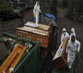 Workers collect and stack the coffins of people that have been recently cremated amid the new coronavirus pandemic at La Recoleta cemetery, in Santiago, Chile, Monday, July 6, 2020. The coffins are collected and destroyed by a company specializing in organic waste. (AP Photo/Esteban Felix)