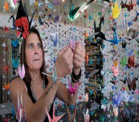 Artist Karla Funderburk, owner of Matter Studio Gallery, adjusts one of of the thousands of origami cranes hanging during an exhibit honoring the victims of COVID-19, Tuesday, Aug. 11, 2020, in Los Angeles. Funderburk started making the cranes three months earlier, stringing the paper swans in pink, blue, yellow and many other colors together and hanging them in her gallery. (AP Photo/Richard Vogel)