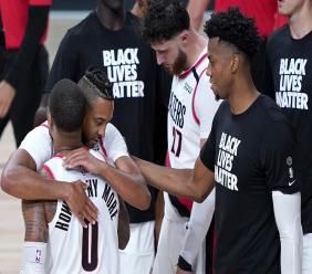 Portland Trail Blazers' Damian Lillard (0) is hugged by teammate CJ McCollum after defeating the Brooklyn Nets during an NBA basketball game Thursday, Aug. 13, 2020, in Lake Buena Vista, Fla. The Trail Blazers won 134-133. (AP Photo/Ashley Landis, Pool).