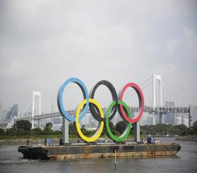 """A symbol installed for the Olympic and Paralympic Games Tokyo 2020 on a barge is moved away from its usual spot by tugboats off the Odaiba Marine Park in Tokyo Thursday, Aug. 6, 2020. The five Olympic rings floating on a barge in Tokyo Bay were removed for what is being called """"maintenance,"""" and officials says they will return to greet next year's Games.  (AP Photo/Hiro Komae)."""