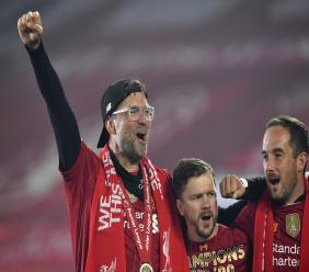 Liverpool's manager Jurgen Klopp, left, celebrates after the English Premier League trophy was presented at the teams last home game of the season against Chelsea  at Anfield Stadium in Liverpool, England, Wednesday, July 22, 2020. Liverpool won the match against Chelsea 5-3. (Paul Ellis, Pool via AP).