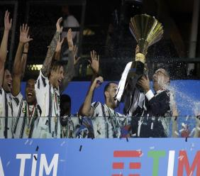 Juventus' head coach Maurizio Sarri, right, holds up the trophy while players celebrate winning an unprecedented ninth consecutive Italian Serie A football title, at the end of the a Serie A match against Roma at the Allianz stadium in Turin, Italy, Saturday, Aug.1, 2020. (AP Photo/Luca Bruno).