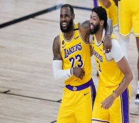 Los Angeles Lakers' LeBron James (23) and Anthony Davis (3) celebrate after defeating the Denver Nuggets 124-121 during an NBA basketball game Monday, Aug. 10, 2020, in Lake Buena Vista, Fla. (AP Photo/Ashley Landis, Pool).