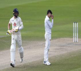 Pakistan's Naseem Shah, right, reacts as England's Chris Woakes, left, runs between the wickets to score during the fourth day of the first cricket Test at Old Trafford in Manchester, England, Saturday, Aug. 8, 2020. (Lee Smith/Pool via AP).