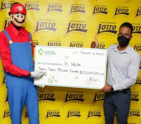 Supreme Ventures' Vice President of Product Management and Business Development, Stefan Miller presents H. Wilson with his $33 million Lotto jackpot at SVL in New Kingston.