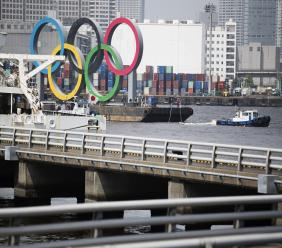 """Tugboats move a symbol installed for the Olympic and Paralympic Games Tokyo 2020 on a barge from its usual spot off the Odaiba Marine Park in Tokyo Thursday, Aug. 6, 2020. The five Olympic rings floating on a barge in Tokyo Bay were removed what is being called """"maintenance,"""" and officials says they will return to greet next year's Games.  (AP Photo/Hiro Komae)."""