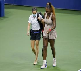 In this Sept. 10, 2020, file photo, Serena Williams walks to her bench with a trainer for a medical timeout during a semifinal match of the US Open tennis championships, against Victoria Azarenka, of Belarus, in New York. (AP Photo/Seth Wenig, File).