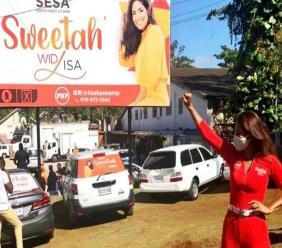 In a photo posted to her social media during the general elections campaign, Lisa Hanna raises a fist in front of a billboard bearing her image.