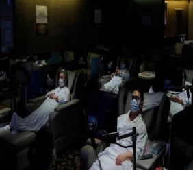 Staff members wearing face masks demonstrate the safety measures to media as the massage spa plan to be reopened in Hong Kong, Thursday, Sept. 17, 2020. Government officials said that it would further relax social-distancing measures, allowing bars, amusement parks and swimming pools to re-open. (AP Photo/Kin Cheung)