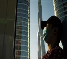 FILE - In this April 26, 2020 file photo, a commuter wearing a face mask to help curb the spread of the coronavirus, sleeps aboard the driverless Metro as it passes the Burj Khalifa, the world's tallest building, in Dubai, United Arab Emirates.  (AP Photo/Jon Gambrell, File)