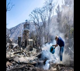 Dale Burton, of Leona Valley, tries to put out the fire that continues to smolder at his friend Cheryl Poindexter's property on Monday, Sept. 21, 2020 after the Bobcat fire burned her home of 27 years and the 11 acre property where she ran an animal rescue in Juniper Hills, Calif. (Sarah Reingewirtz/The Orange County Register via AP)