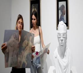 "In this Dec. 6, 2018, file photo, two people look at the artist Hajar Benjida's project called ""Young Thug as Paintings"" at the Scope Miami Beach gallery during Art Basel in Miami Beach, Fla.  (AP Photo/Brynn Anderson, File)"
