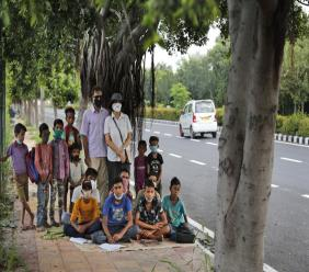 A former diplomat Virendra Gupta and his singer wife Veena Gupta pose for a photograph with underprivileged children whom they teach on a sidewalk in New Delhi. (AP Photo/Manish Swarup)
