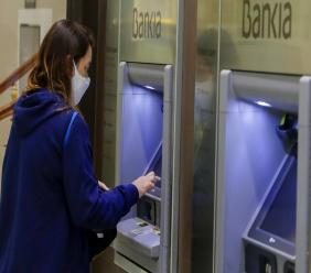 A woman uses an ATM cash point machine at a branch of the Bankia bank in Madrid, Spain.(AP Photo/Manu Fernandez)