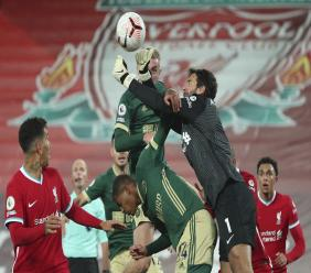 Liverpool's goalkeeper Alisson punches clear as Sheffield United's Oliver McBurnie during their English Premier League football match at Anfield in Liverpool, England, Saturday, Oct. 24, 2020. (Peter ByrnePool via AP).