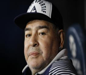 In this March 7, 2020 file photo, Diego Maradona, coach of Gimnasia y Esgrima, sits on the bench prior to Argentina's football league match against Boca Juniors at La Bombonera stadium in Buenos Aires, Argentina. (AP Photo/Natacha Pisarenko, File).