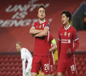 Liverpool's Diogo Jota, 20, celebrates scoring his side's first goal with Takumi Minamino, right, during the Champions League Group D football match against FC Midtjylland at Anfield stadium, in Liverpool, England, Tuesday, Oct. 27, 2020. (Michael Regan/Pool via AP).