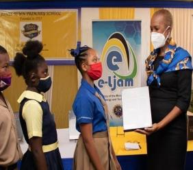 Education Minister Fayval Williams and three of the beneficiaries during the recent handing over ceremony.