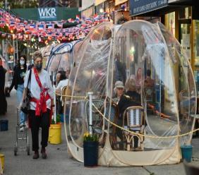 Des personnes dînent sous des tentes en plastique dans le quartier de Manhattan, le 15 octobre 2020 à New York Angela Weiss AFP/Archives