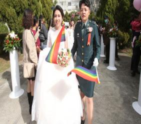 Lesbian couple Yi Wang, right, and Yumi Meng show their wedding rings during a military mass weddings ceremony in Taoyuan city, northern Taiwan, Friday, October 30, 2020. (AP Photo/Chiang Ying-ying)
