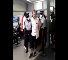 A man being escorted by police inside the Norman Manley International Airport in Kingston after he allegedly hurled racist insults at a passengers on a plane.