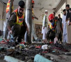 Pakistani rescue workers and police officers examine the site of a bomb explosion in an Islamic seminary, in Peshawar, Pakistan, Tuesday, October 27, 2020. (AP Photo/Muhammad Sajjad)