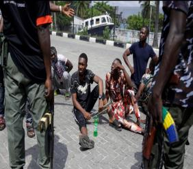 Police officers stop and search a bus carrying passengers around Lekki toll gate in Lagos Friday, October 23, 2020. Resentment lingered with the smell of charred tires Friday as Nigeria's streets were relatively calm after days of protests over police abuses, while authorities gave little acknowledgement to reports of the military killing at least 12 peaceful demonstrators earlier this week. (AP Photo/Sunday Alamba)