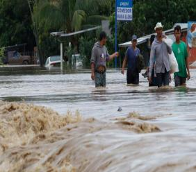 Men wade through a street flooded after the passing of Hurricane Iota in La Lima, Honduras, Wednesday, November 18, 2020.  (AP Photo/Delmer Martinez)