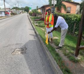 President of the Barbados Road Safety Sharmane Roland-Bowen and Acting Vice President Wilton Gale placing a flag indicating the pothole near PriceLo Supermarket in Christ Church.